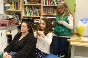 Student Katherine Gaudio gets into the spirit by styling speech-language pathologist Emily Teed's hair, while speech-language pathologist Sara Pisarchik works on hers.