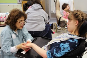 Volunteer Renee Bloom gives a hand massage to student Tammy Boszczuk.