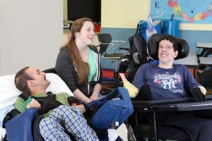 Adult residents Luis Rodriguez, left, and Andy Lash enjoy the music along with music therapy intern Kaitlyn Anastasi.
