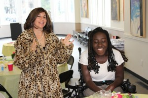 Matheny trustee and parent Edana Desatnick, left, models a coat purchased by Matheny student Raven Bennett, right. Bennett volunteers at the 2nd Chance Shop.